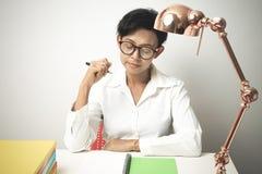 La mujer que piensa y hace una pluma y una libreta colocar Imagen de archivo libre de regalías