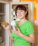 La mujer que pone con el metal puede acercar al refrigerador foto de archivo libre de regalías