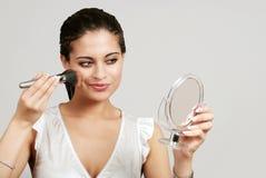La mujer que pone en maquillaje con se ruboriza cepillo Foto de archivo libre de regalías