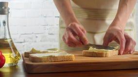 La mujer que prepara los bocadillos y las extensiones untan con mantequilla en el pan, vídeo 4k almacen de metraje de vídeo