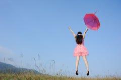 La mujer que salta al cielo azul con el paraguas rojo Fotos de archivo libres de regalías
