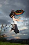 La mujer que salta con el paraguas del arco iris Imagen de archivo