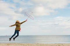 La mujer que salta con el paraguas transparente en la playa Fotografía de archivo