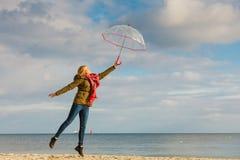 La mujer que salta con el paraguas transparente en la playa Imagen de archivo libre de regalías