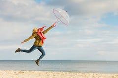 La mujer que salta con el paraguas transparente en la playa Fotos de archivo libres de regalías