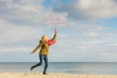 La mujer que salta con el paraguas transparente en la playa Imagen de archivo