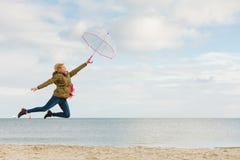La mujer que salta con el paraguas transparente en la playa Imágenes de archivo libres de regalías