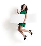 La mujer que salta con la muestra en blanco Fotografía de archivo