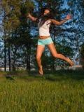 La mujer que salta en campo Imagen de archivo libre de regalías