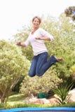 La mujer que salta en el trampolín en jardín Imagenes de archivo