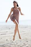 La mujer que salta en la arena Foto de archivo libre de regalías