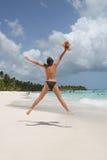 La mujer que salta en la playa Foto de archivo