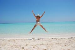 La mujer que salta en la playa Imagen de archivo