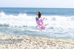 La mujer que salta en la playa Foto de archivo libre de regalías