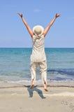 La mujer que salta en la playa Fotografía de archivo libre de regalías