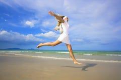 La mujer que salta en la playa Imagen de archivo libre de regalías