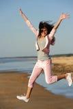 La mujer que salta en la playa Imágenes de archivo libres de regalías