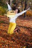 La mujer que salta en parque del otoño Fotos de archivo libres de regalías