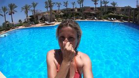 La mujer que salta en una piscina de agua azul metrajes