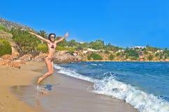 La mujer que salta en una playa griega Foto de archivo libre de regalías