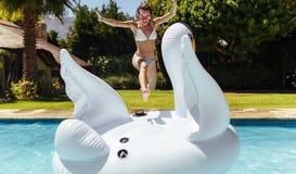 La mujer que salta encendido a un juguete inflable en piscina Imagenes de archivo