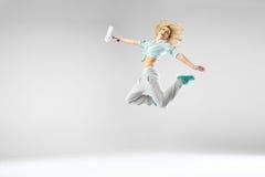 La mujer que salta y que sostiene un rodillo blanco Imágenes de archivo libres de regalías