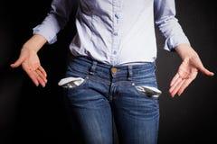 La mujer que señala en sus pantalones vacia los bolsillos Fotos de archivo libres de regalías