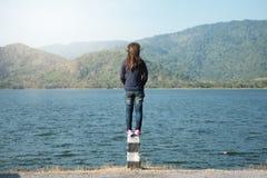 La mujer que se coloca en el frente del borde de la carretera del pilar de ella tiene lago grande y Foto de archivo