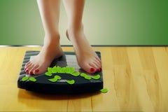 La mujer que se coloca en escalas, peso pierde fotos de archivo