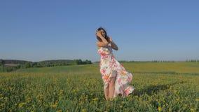 La mujer que se coloca en un campo amarillo floreciente en un vestido aumenta los brazos y el torneado metrajes