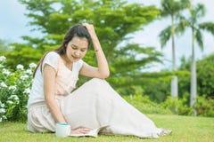 La mujer que se sienta en campo de hierba en el jardín público para leer por la mañana, relaja época de la mujer asiática Fotografía de archivo libre de regalías