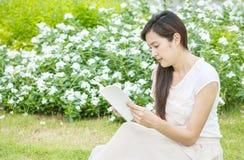 La mujer que se sienta en campo de hierba en el jardín público para leer por la mañana, relaja época de la mujer asiática Fotografía de archivo