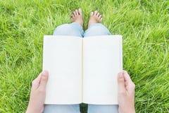 La mujer que se sienta en campo de hierba en el jardín público para leer por la mañana, relaja época de la mujer asiática Foto de archivo libre de regalías