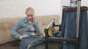 La mujer que se sienta en el sofá habla en el teléfono y examina una colección de vaqueros que cuelga en la suspensión almacen de video
