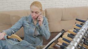 La mujer que se sienta en el sofá habla en el teléfono y examina una colección de vaqueros que cuelga en la suspensión metrajes