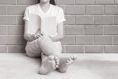 La mujer que se sienta en la esquina de la casa para leer un libro blanco en tiempo libre por la tarde, relaja época de la mujer  Fotografía de archivo