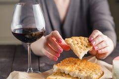 La mujer que se sienta en la tabla goza de una gota y de un vidrio de vino rojo Fotografía de archivo