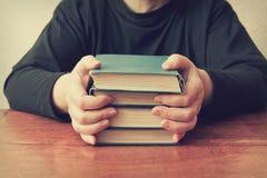 La mujer que se sienta en la tabla y guarda una pila de libros viejos Foto de archivo