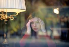 La mujer que se sienta en la ventana y meditate foto de archivo libre de regalías