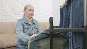 La mujer que se sienta en un sofá examina una colección de ropa del dril de algodón que cuelga en una suspensión almacen de video