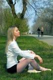 La mujer que se sienta en una hierba Fotos de archivo libres de regalías