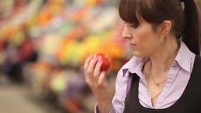 La mujer que selecciona la fruta en el mercado del granjero y añade almacen de metraje de vídeo