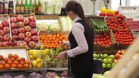 La mujer que selecciona la fruta en el mercado y añade al carro almacen de metraje de vídeo
