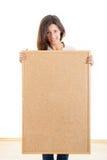 La mujer que sostenía un corcho del tablero de madera aisló en el fondo blanco a Imagen de archivo libre de regalías