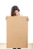 La mujer que sostenía un corcho del tablero de madera aisló en el fondo blanco a Foto de archivo libre de regalías