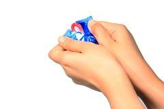 La mujer que sostiene el condón disponible, mano que sostiene un condón en paquete, es Fotos de archivo libres de regalías