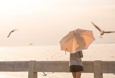 La mujer que sostiene el paraguas mira gaviotas Imágenes de archivo libres de regalías