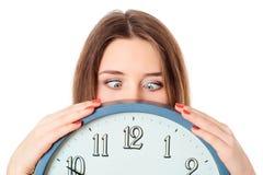 La mujer que sostiene el reloj con preguntarse observa absurdo Imagen de archivo libre de regalías