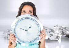 La mujer que sostiene el reloj del cromo delante del diente de la plata del cromo rueda Fotos de archivo libres de regalías