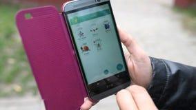 La mujer que sostiene el teléfono de HTC y que juega Pokemon va almacen de video